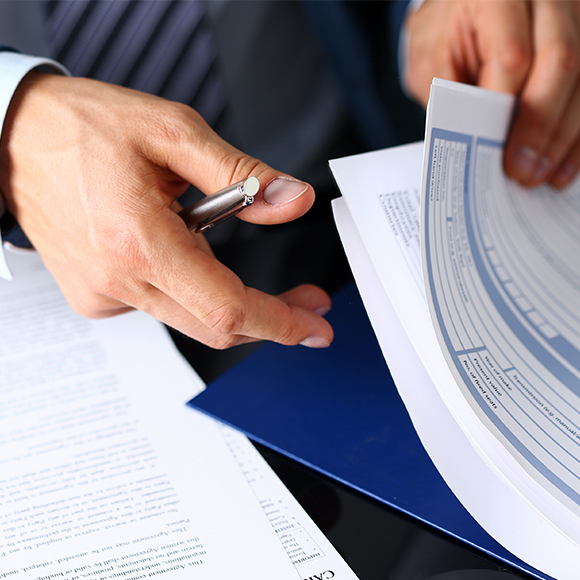 Business owner looking through documentation to promote professional indemnity insurance by Evalee Insurance Brokers