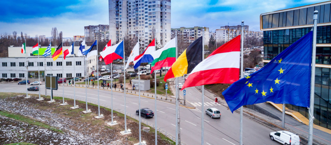 Cars driving down a motorway lined with various European flags to promote Car Insurance and Green Cards by Evalee Insurance brokers