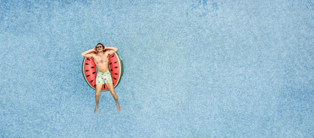 Man floating on swimming pool on a watermelon print rubber ring to promote Travel Insurance by Evalee Insurance brokers