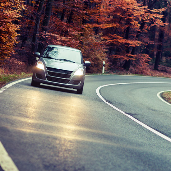 Car driving down quiet road in Autumn to promote car insurance by Evalee Insurance Brokers