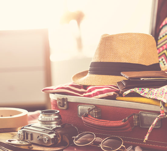 Packed suitcase laying open on bed, complete with a straw hat, camera and sunglasses to promote travel insurance by Evalee Insurance Brokers